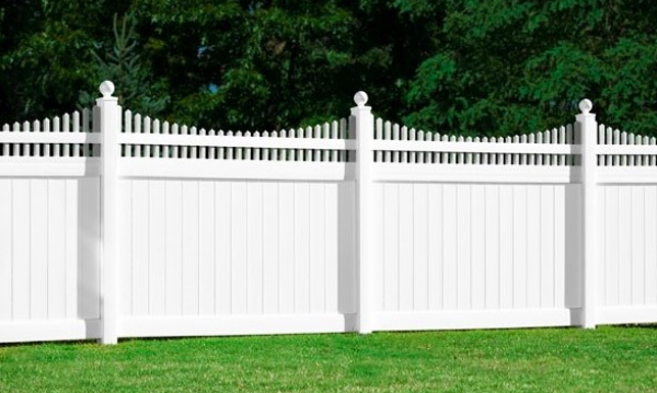A white picket-style vinyl privacy fence