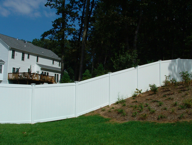 A vinyl fence racked to follow a slope