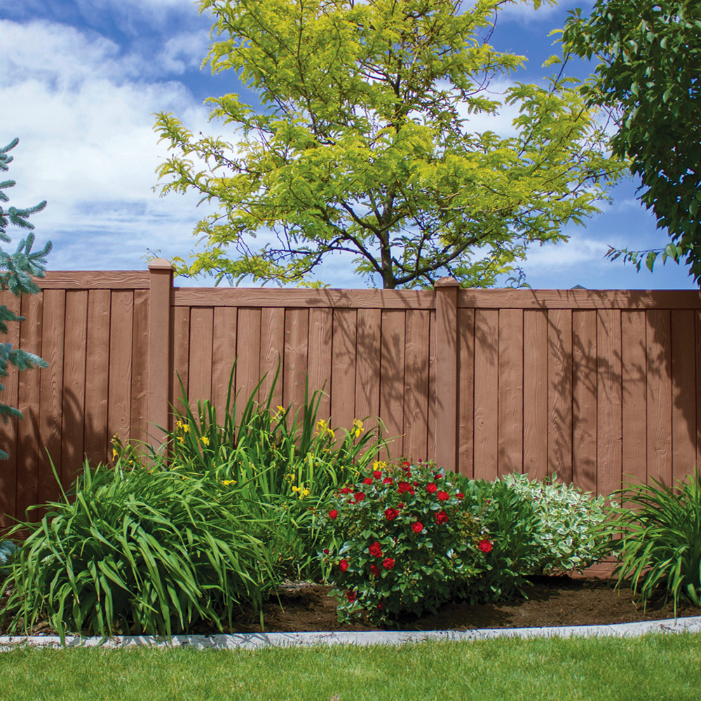 Vinyl fence next to plants and tree