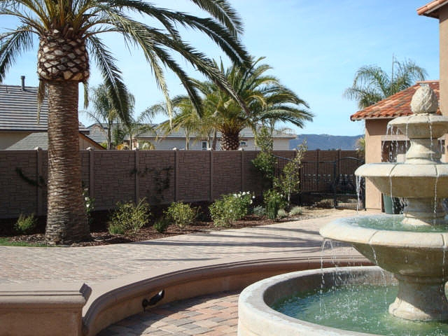a backyard with a vinyl fence, water fountain and palm trees
