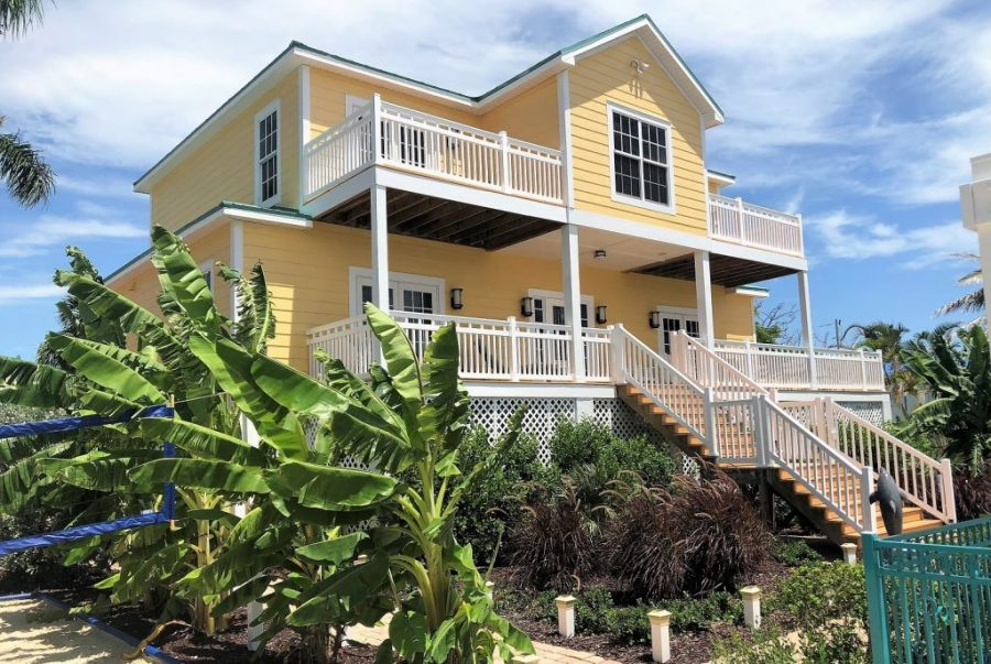 Yellow two-story home with white railings surrounding the deck, patio and staircase