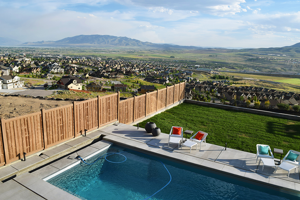 Vinyl wood fence in a yard with a pool overlooking a neighborhood in a mountain valley