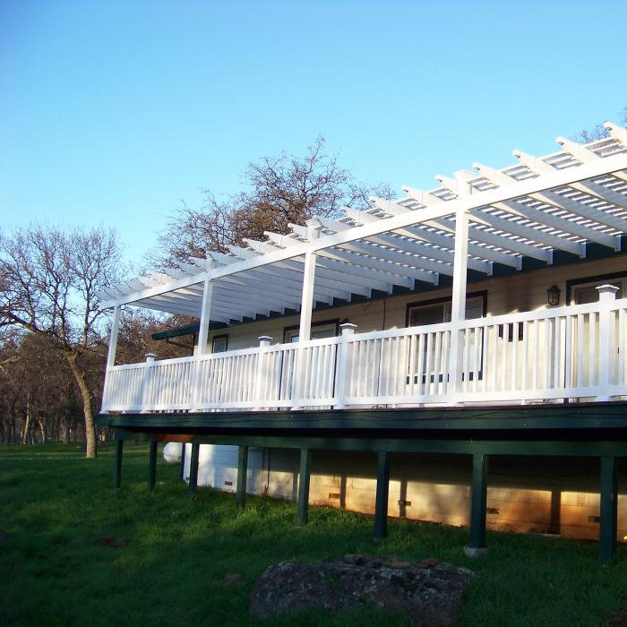 White vinyl pergola attached to a home's deck