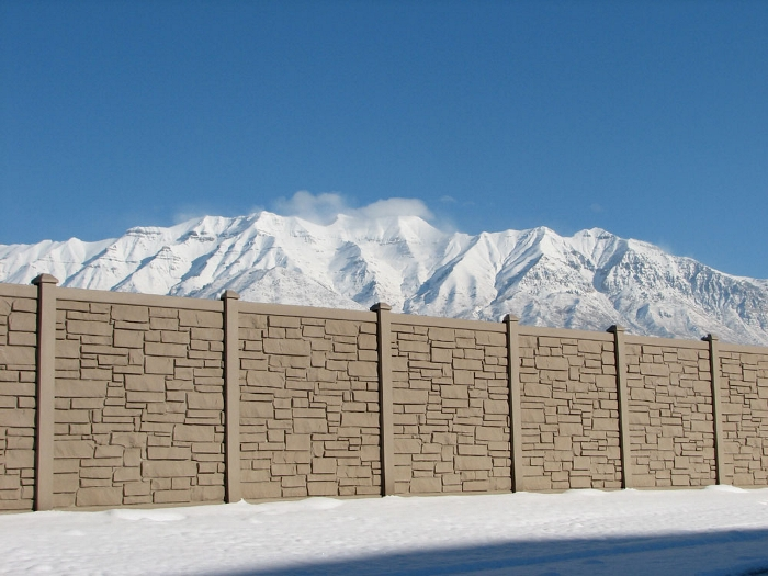 A simulated stone fence surrounded by snow with a mountain in the background