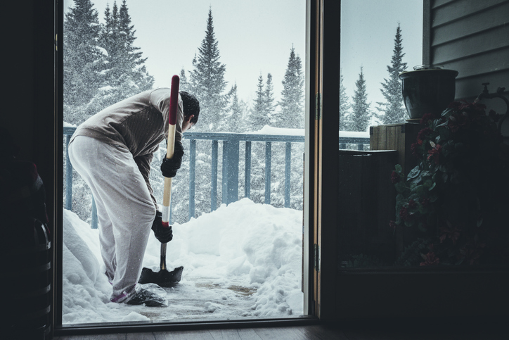 Person shoveling snow off their deck with a plastic shovel