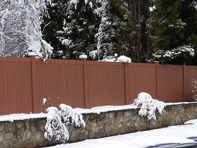 A mocha walnut colored wood grain vinyl privacy fence surrounded by snow in a yard