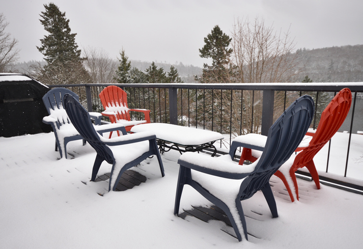 Deep snow covering a table and chairs on a vinyl deck