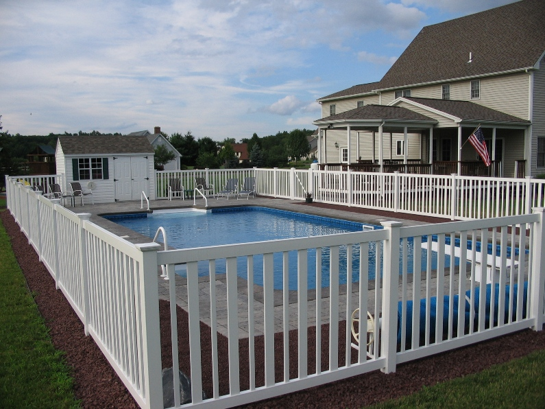 A white seneca pool fence around a private inground pool in the back yard