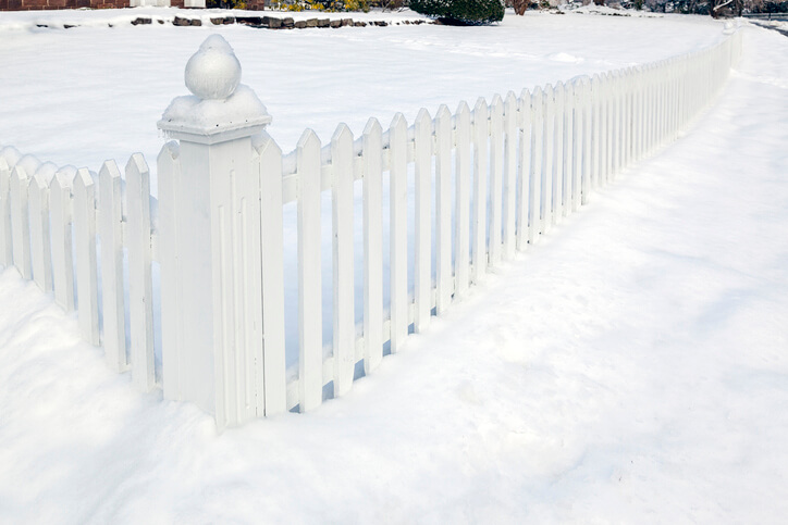 White vinyl fence half buried in snow