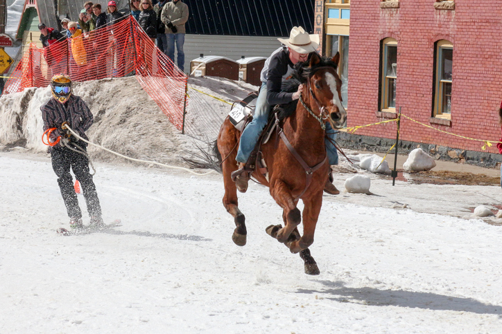 Skijoring event with a person riding a horse pulling a skier across snow