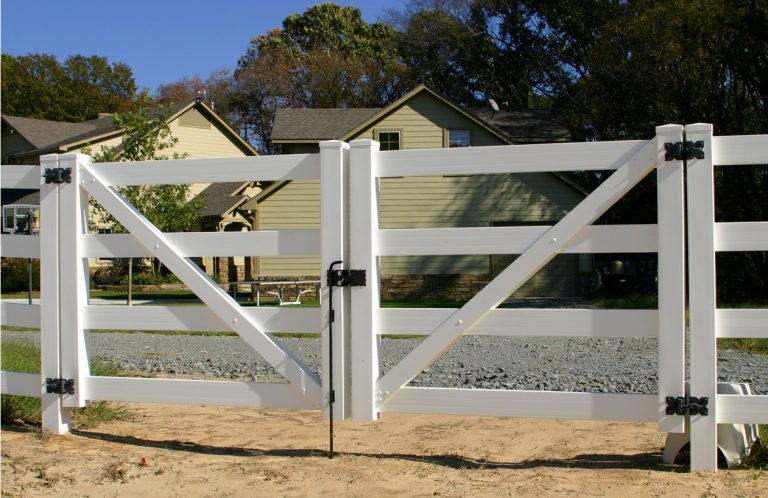 White vinyl fence gate with a drop rod lock on a horse ranch